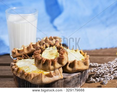 Karelian Pirakka Pies Located On A Wooden Stand. In The Background Is A Glass Of Milk. Traditional D