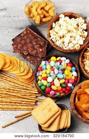 Salty Snacks. Pretzels, Chips, Crackers In Wooden Bowls And Candy And Chocolate On Table