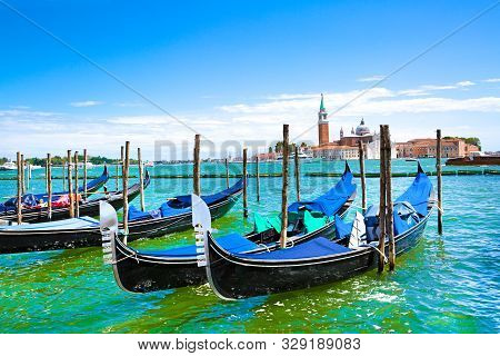 Gondolas And Bright Turquoise Water Of Canal. Grand Canal In Venice, Italy. Sunny Summer Vacations.