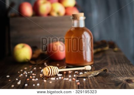 Honey Dipper With Honey Surrounded By Pink Himalayan Salt. Apple Cider Vinegar, With The Mother, And
