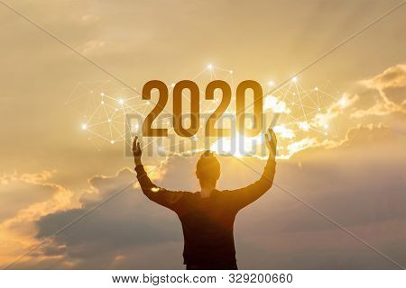 The New Concept 2020. The Woman Shows The Numbers 2020 At Sunset.