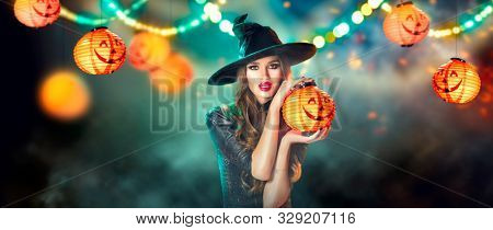 Halloween Witch holding Pumpkin lantern in a dark forest decorated with garlands and hanging Jack-o-Lantern Pumpkins. Beautiful young woman in witches hat and costume. Halloween party art design