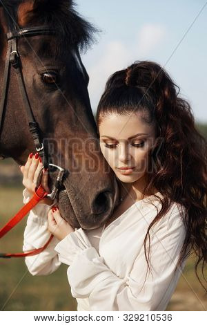 Girl In A Long Dress Stands Near A Horse, A Beautiful Woman Strokes A Horse And Holds The Bridle In