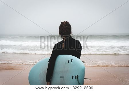 Young Girl Server Stands With A Surfboard By The Ocean. Stormy Weather.