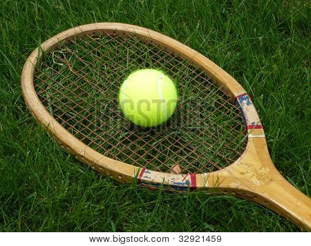 Old tennis racket with ball on grass court
