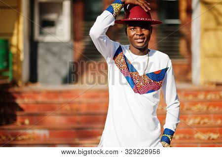 Stylish Trendy Afro France Man In Red Hat And White Outfit Posed At Autumn Day. Black African Model