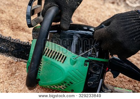 Professional Technician Working By Repair Service.repairing Chainsaw In Repair Shop.