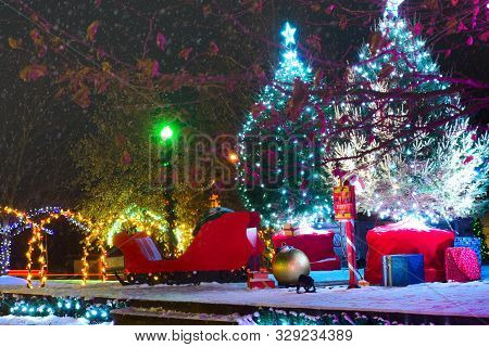 An Outdoor Christmas Display With A Sleigh, Wrapped Presents, And Lighted Arches On A Snowy December