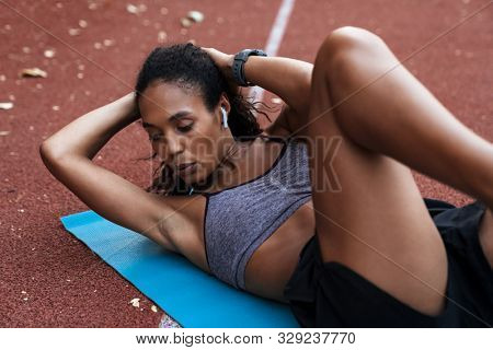 Image of healthy african american woman in sportswear doing criss cross crunches at fitness mat outdoors