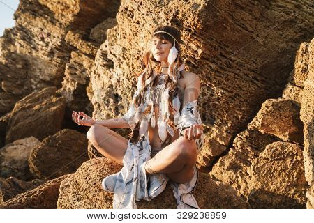 Image of cute hippy girl in feather headband meditating while sitting by rock in morning