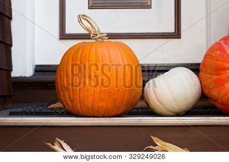 Two Orange, And One White Pumpkin On Display In Front Of A Door