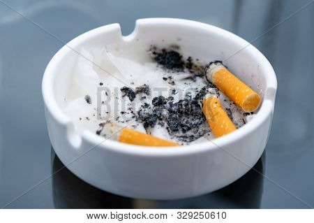 White dirty ashtray with cigarette stubs. Cigarette butts poster