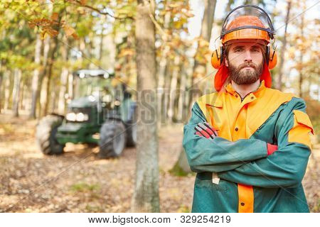 Self-confident forest worker or forestry worker in protective clothing during forest work