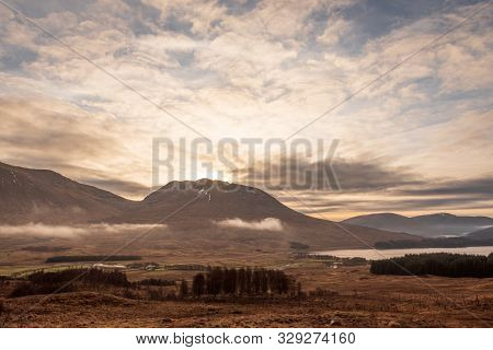 A View Of The Wintery Grass Fields In The Scottish Highlands As The Sun Sets Over A Mountain On A Cl