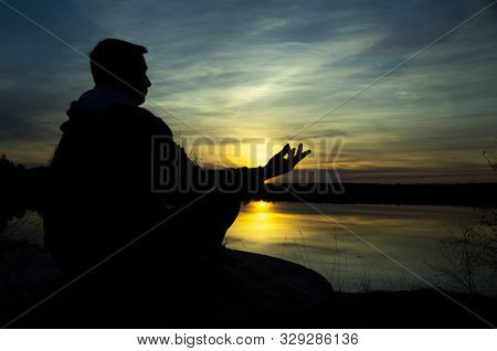 Silhouette Of A Meditating Man . Meditation As A Way To Relax.