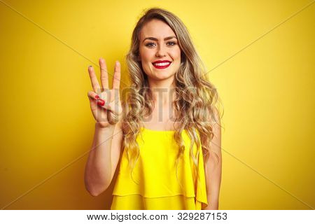 Young attactive woman wearing t-shirt standing over yellow isolated background showing and pointing up with fingers number three while smiling confident and happy.