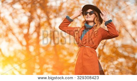Beautiful happy young woman in autumn park on a sunny day. Beauty, fashion.