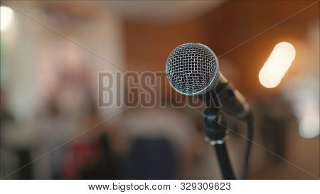 Microphone On Stage Against A Background Of Auditorium. Stage Microphone. Open Microphone