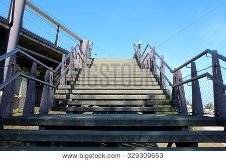 Outdoor Wide Concrete Stairs Surrounded With Inox Handrails And Wire Net Protection Leading To Local