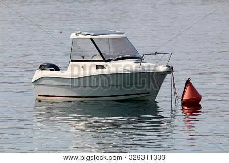 Small Fishing Boat With Modern Solar Panel On Top And Inox Rail In Front Tied To Large Red Buoy In L