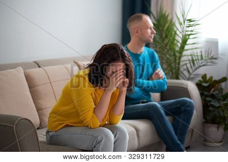 Sad Wife And Husband, Angry Couple In Bedroom. Unhappy Couple Concept. Usband And Wife Are Sitting O