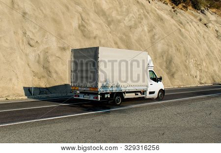 A Semi-truck On The Street Near The Mountain. Small Freight Truck On A Road. White Truck Without Log