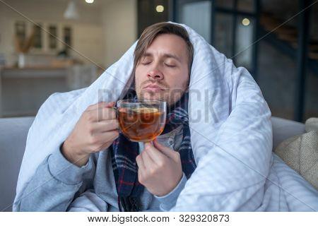 Sick Man Smelling Lemon While Drinking Hot Tea