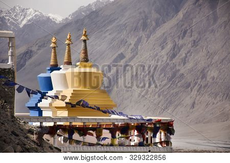 Colorful Three Stupa Or Chedi In Maitreya Buddha Statue And Diskit Monastery Perched Against The Hil