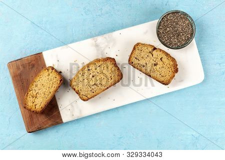 Chia Seeds Cake, Shot From The Top On A Marble Cutting Board And A Blue Background With A Place For