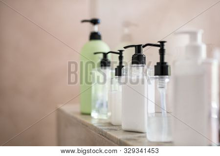 Dispenser bottles in a row kept on rack in bathroom. Close up of multiple shampoo, soap and body lotion bottles on marble at spa. Bottle of soap and liquid in bathroom.