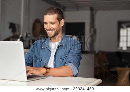 Happy young businessman using laptop at home. Young man working on computer at home. Casual entrepreneur feeling excited about new project while working on laptop at home.