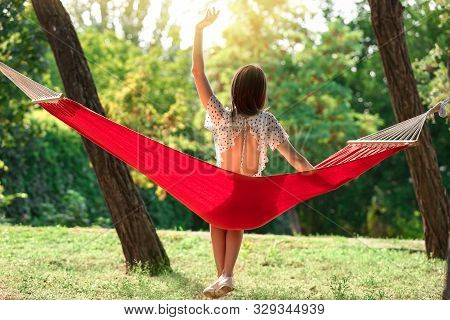Happy Young Woman Sitting In Hammock Outdoors