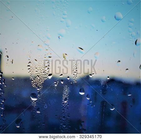 Raindrops On The Windowpane. Autumn Cityscape Through The Window. Rainy Evening.