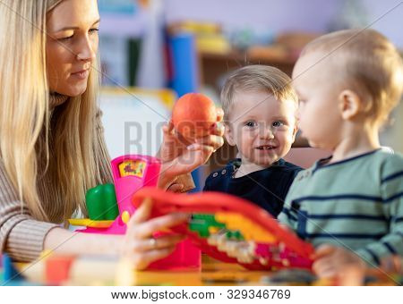 Children Toddlers And Nursery Teacher Play With Toy Scales In Kindergarten Playroom