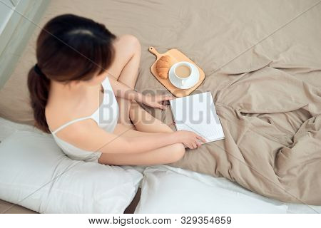 Young Woman Sitting In Bed While Reading A Book With Coffee Cup