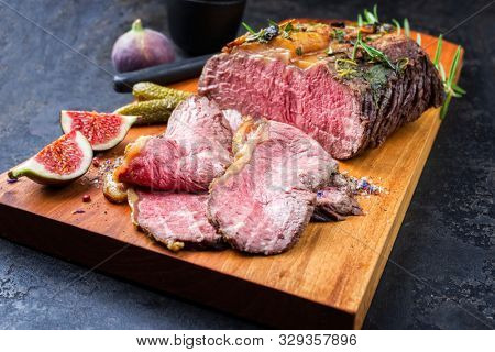 Traditional lunch meat with sliced cold cuts roast beef with gherkin and fig fruit as closeup on a modern design cutting board