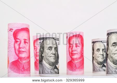 Rolls of many 100 US dollar and 100 Chinese yuan renminbi banknotes on white background. poster
