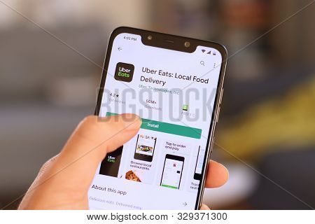 Warsaw, Poland - October 22, 2019: User Installing Uber Eats Food Delivery App On A Xiaomi F1 Pocoph