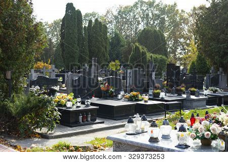 Graves At A Christian Cemetery In Autumn. All Saints Day. Tombstones Decorated With Flowers And Grav