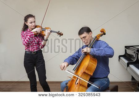 Musicians Of The Symphony Orchestra. Young Violinist And Cellist In Concert Costumes.