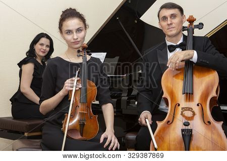Family Music Trio. A Young Violinist And Cellist Play, The Pianist Accompanies Them.
