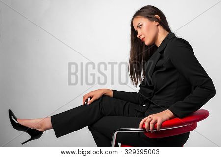 Young Beautiful Girl In Business Suit Black Jacket, Pants, Shoes Sitting On Red Chair, White Backgro