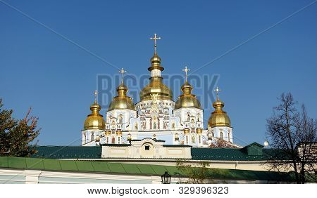 Domes Of St. Michaels Golden-domed Cathedral In Kiev Against A Blue Sky