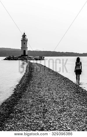 Vladivostok, Russia - July 30, 2015: Young Girl Is Walking To The Lighthouse. The Old Japanese Light
