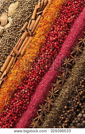 Various Spices And Herbs Are Scattered On Table. Seasoning Background For Packaging With Food. Spice