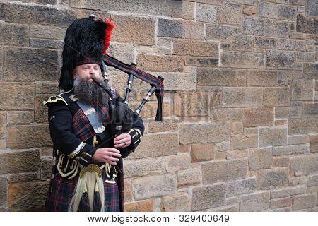 EDINBURGH,UK - AUGUST 14,2019 : Bagpipe player in traditional scottish kilts in Edinburgh