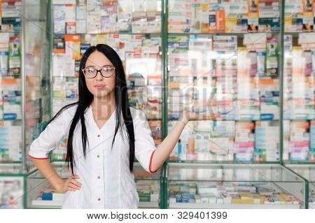 Pharmacy And Pharmacist-seller. Female Pharmacist With Glasses Posing On The Background Of Shop Wind