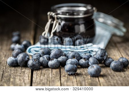 Sweet blueberry jam and blueberries on old wooden table.