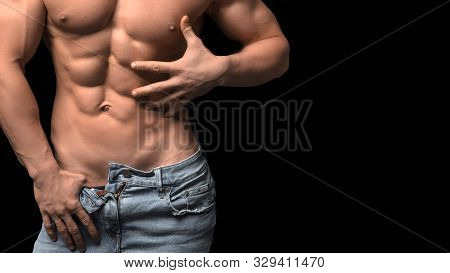 Cropped Image Of A Male Torso In Blue Jeans With Perfect Abs. Sexy Man In Blue Jeans On Dark Backgro