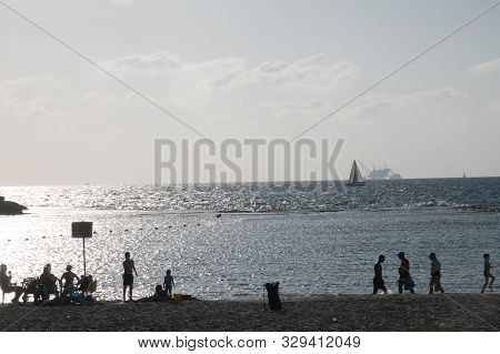 Dor Beach, Israel / 18 Oct 2019: Beachgoers Relaxing On Beach As Sailboat Passes In Front Of Environ